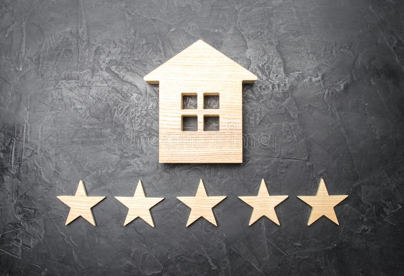 Wooden house and five stars on a gray background. Rating of houses and private property. Buying and selling, renting apartments royalty free stock photo