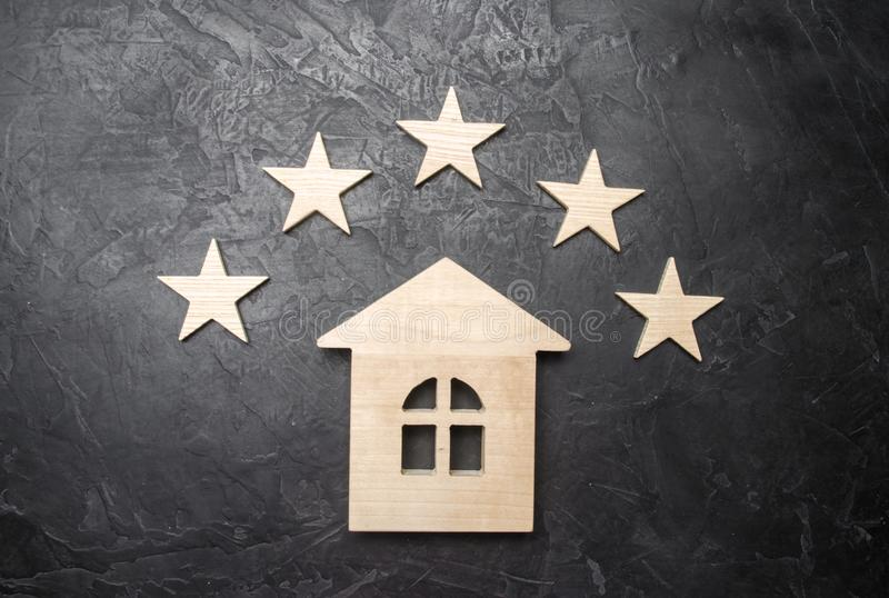 Wooden house and five stars on a gray background. Rating of houses and private property. Buying and selling, renting apartments. The level of the restaurant stock photos