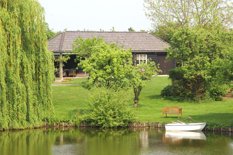 Dutch wooden home, garden and boat along canal, Netherlands royalty free stock photography