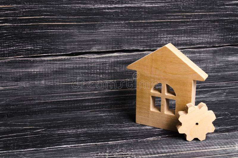 Wooden house with a gear on a background of dark wood. The concept of the enterprise for production, manufactory. Repair stock photos