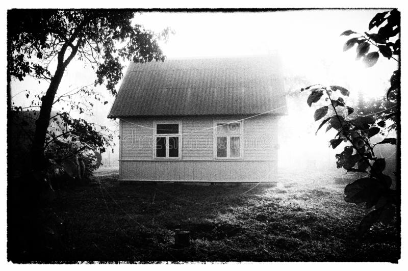 Wooden house and gossamer in foggy morning. Vintage photo imitation. Small rural wooden house and spider web gossamer in the foggy morning. Vintage photography stock images