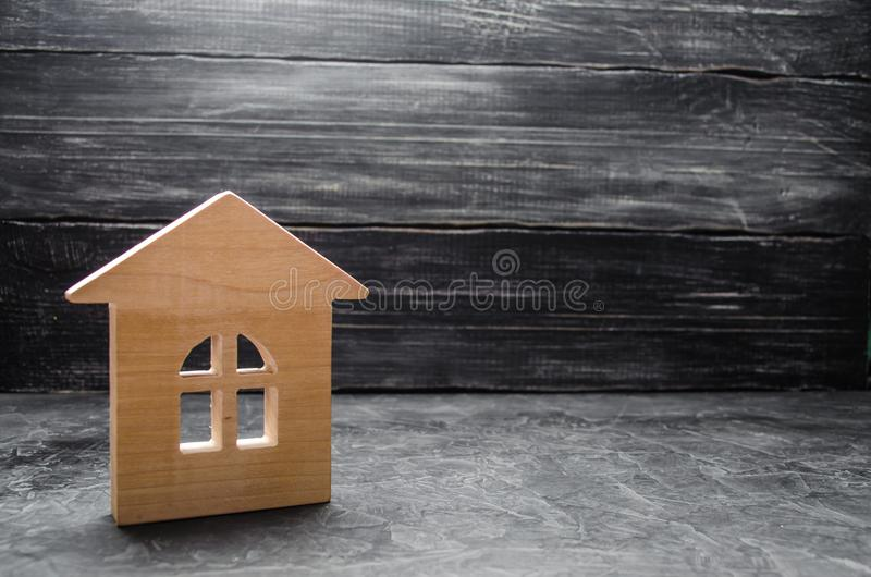 Wooden house on a gray concrete background. Concept of buying and selling housing, building a house. Rent of apartments. Realtors. royalty free stock photography