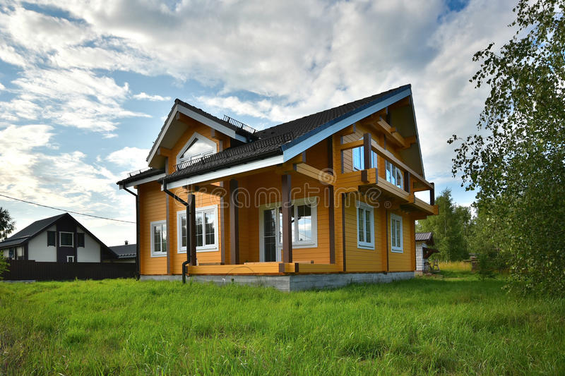 Wooden house on green grass with blue sky. Modern wooden house on green grass with blue sky royalty free stock images