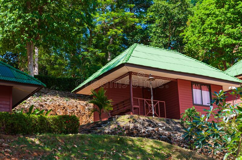 Wooden house with green tiled roof stock photography