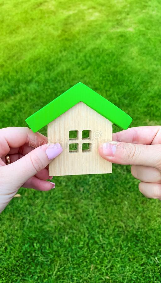 Wooden house in the hand of a young family. Buying a home in a mortgage loan. Real estate concept. Eco friendly home. Government royalty free stock photo