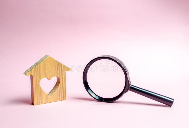 Wooden house with a heart and a magnifying glass. The concept of affordable housing for young families and married couples. Mortgage. Rent a home for a stock photo
