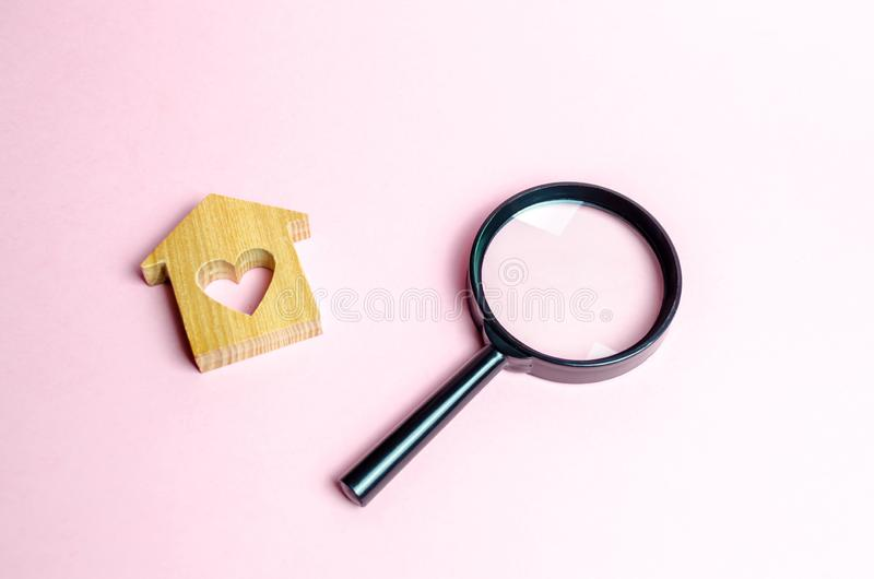 Wooden house with a heart and a magnifying glass. Search and purchase of affordable housing for young families and married couples. Mortgage. Rent a home for a stock photo