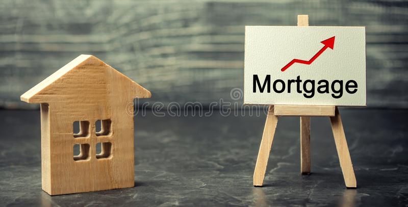 Wooden house and the inscription Mortgage and up arrow. Raising mortgage rates and tax. The increase in interest charges. Reduced. Demand for housing. Loan for royalty free stock images