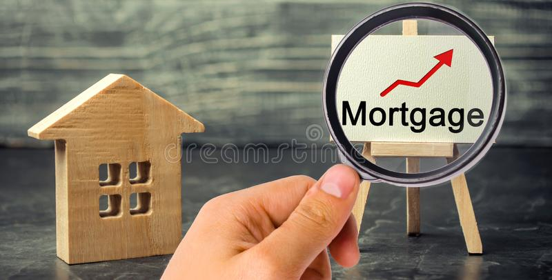 Wooden house and the inscription Mortgage and up arrow. Raising mortgage rates and tax. The increase in interest charges. Reduced. Demand for housing. Loan for stock photo