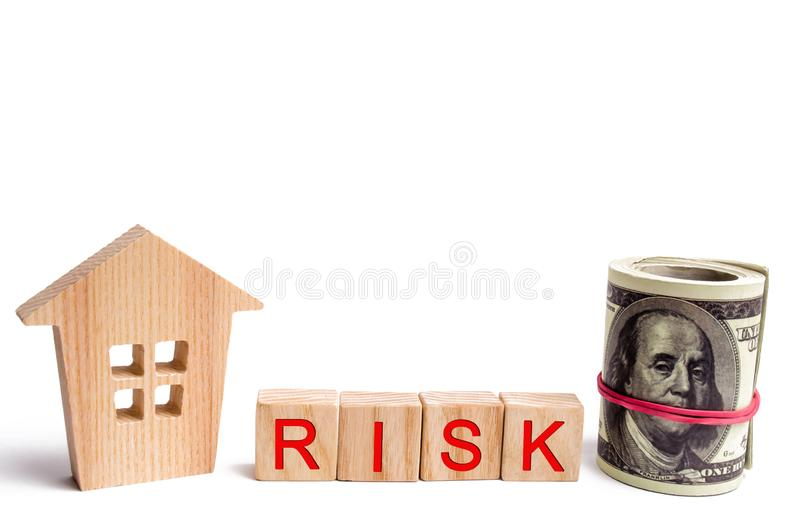 Wooden house and the inscription Risk. The concept of financial risk to buy or sell property. Investment and investment in housing. Buying an apartment in debt royalty free stock image