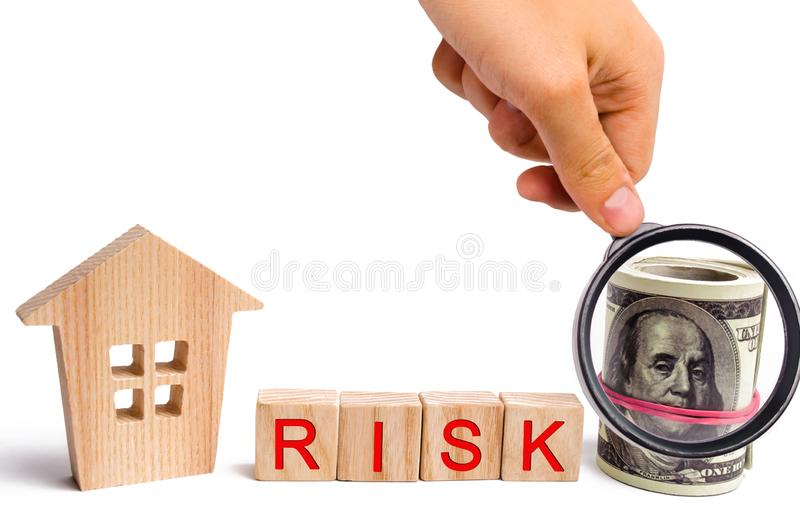Wooden house and the inscription Risk. The concept of financial risk to buy or sell property. Investment and investment in housing. Buying an apartment in debt stock photo