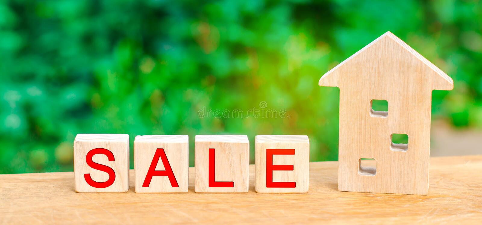 Wooden house with the inscription `sale`. sale of property, home, real estate. affordable housing. Wooden house with the inscription `sale`. sale of property stock images