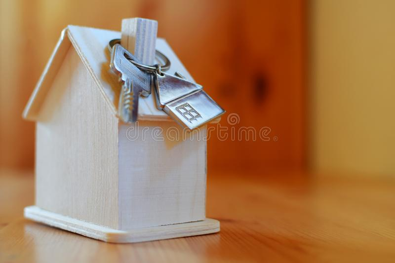 Wooden house with key ring and pendant in shape of home royalty free stock image