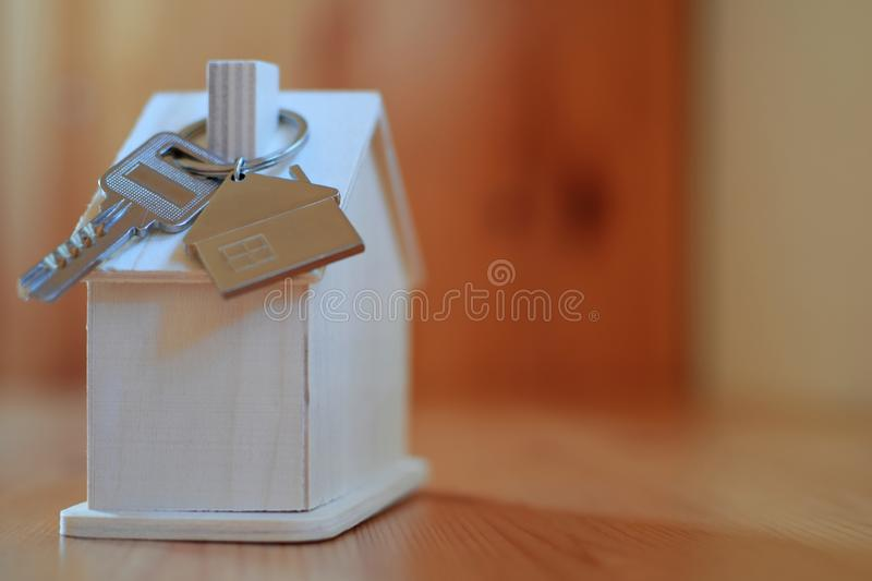 Wooden house with key ring and pendant in shape of home stock photos