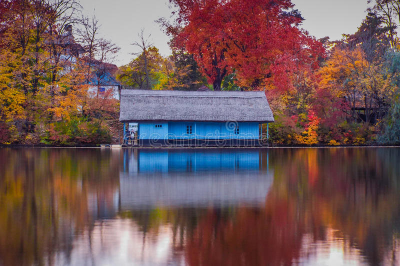 Wooden house on the lake in autumn season royalty free stock photography