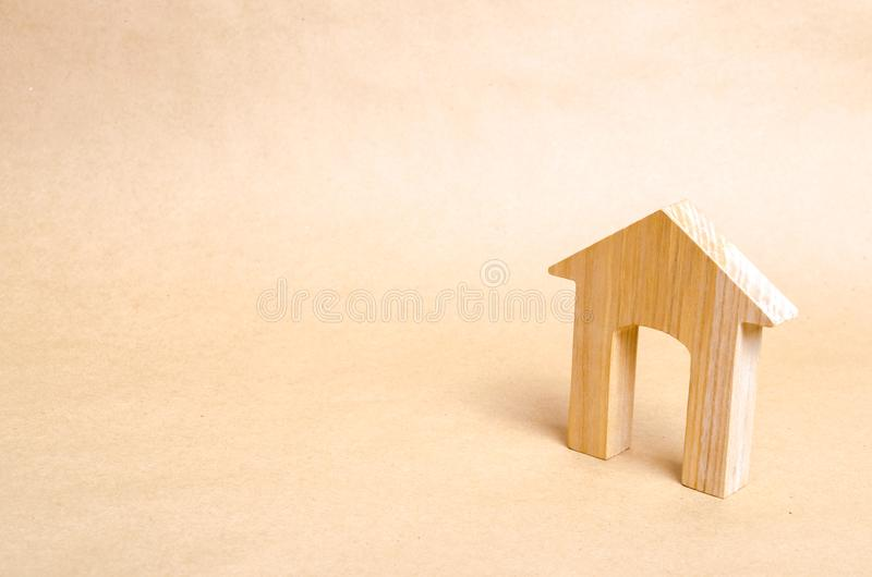 A wooden house with a large doorway stands on a beige paper background. The concept of buying and selling housing. Historical stock photos