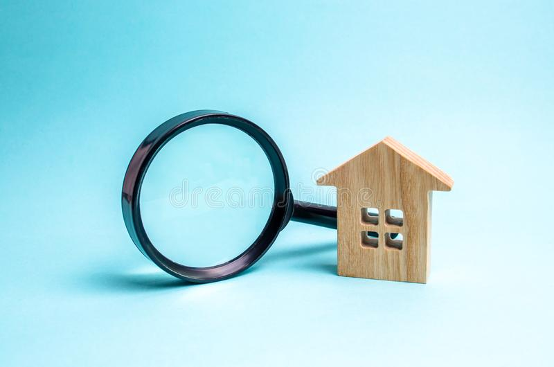 Wooden house and magnifying glass on a blue background. Buying and selling real estate, building new buildings, offices and homes. House search. The concept of stock photos