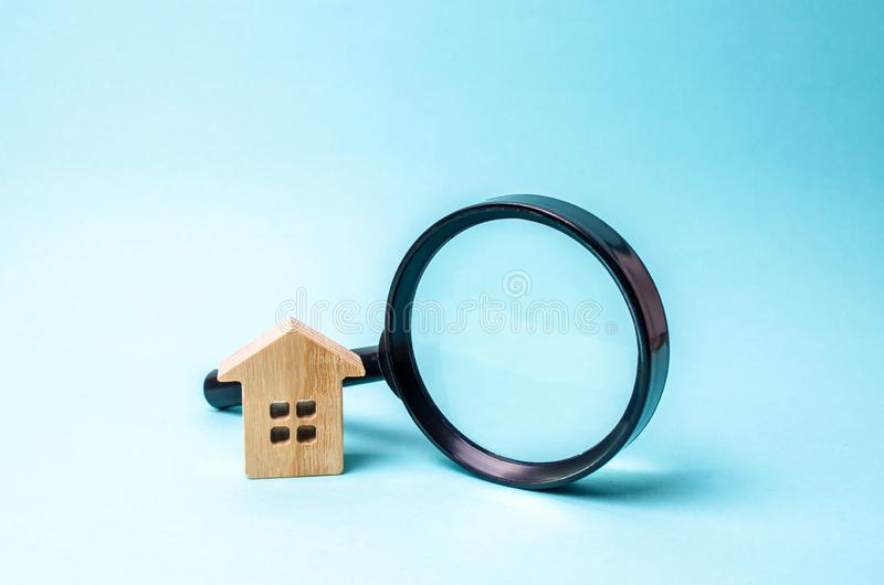 Wooden house and magnifying glass on a blue background. The concept of urban planning, infrastructure projects. Buying and selling. Real estate, building new royalty free stock image
