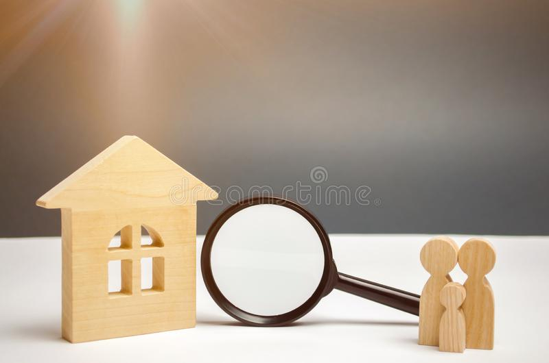 Wooden house and magnifying glass with family. Property valuation. Choice of location for the construction. House searching royalty free stock photo