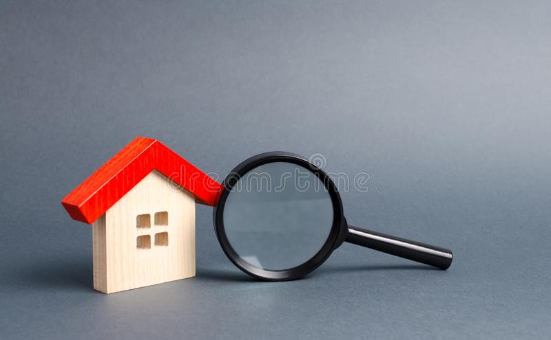 Wooden house and magnifying glass on a gray background. Buying and selling real estate, building new buildings, offices and homes. House search. The concept of stock photos
