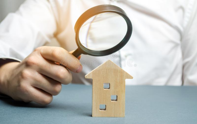 Wooden house and magnifying glass. Property valuation. Choice of location for the construction. House searching concept. Search stock photography