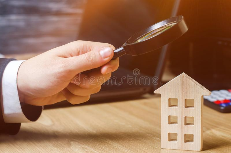 Wooden house and magnifying glass. Property valuation. Choice of location for the construction. House searching concept. Search royalty free stock images