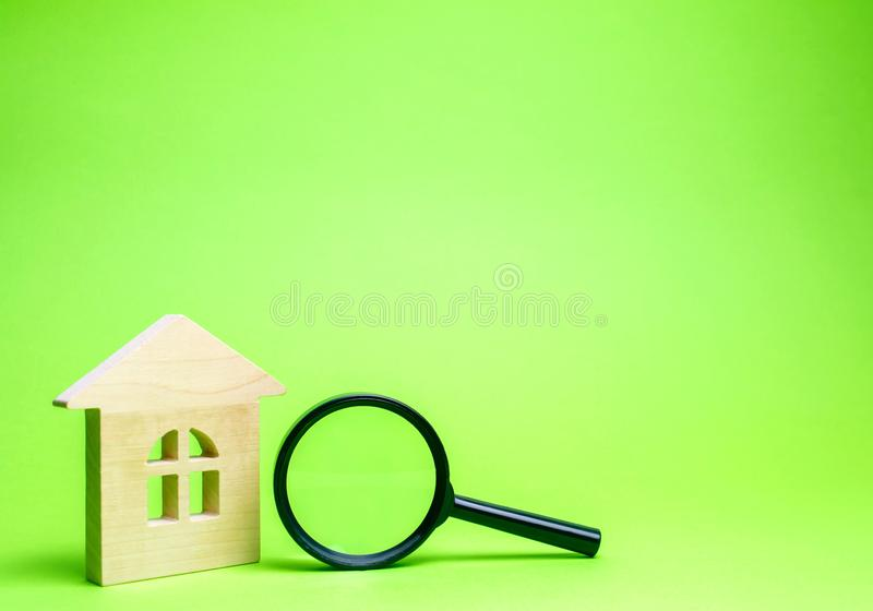 Wooden house and magnifying glass. Property valuation. Choice of location for the construction. House searching concept. Search stock images
