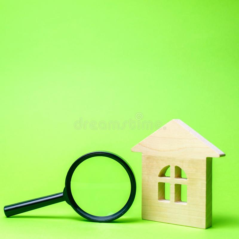 Wooden house and magnifying glass. Property valuation. Choice of location for the construction. House searching concept. Search stock image