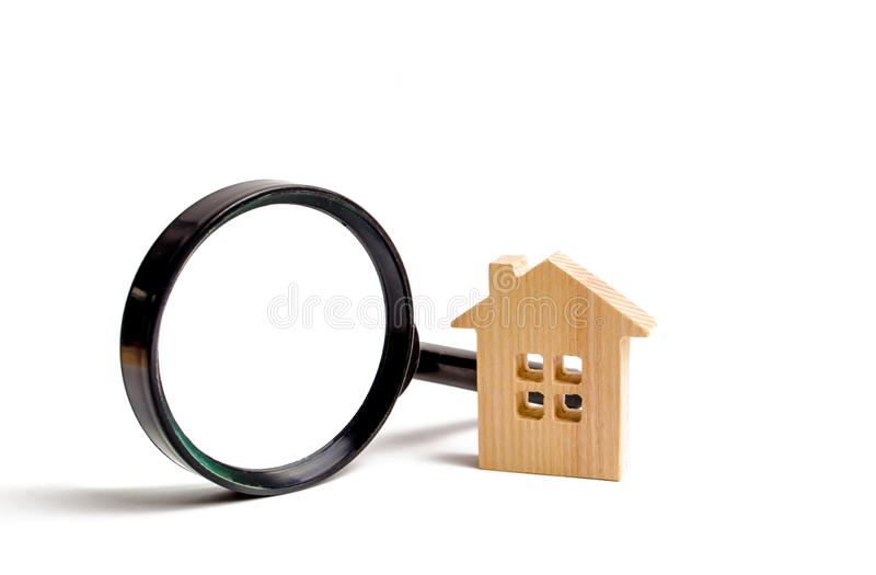 Wooden house and magnifying glass on a white background. Buying and selling real estate, building new buildings, offices and homes. House search. The concept stock photography