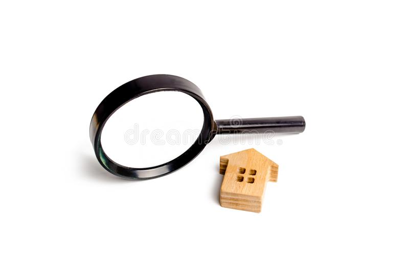 Wooden house and magnifying glass on a white background. Buying and selling real estate, building new buildings, offices and homes. House search. The concept stock photo