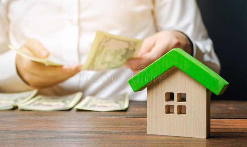 A wooden house and a man who counts money. Real estate concept. Sale and purchase of housing. Mortgage agreement. Payment of debt. For the property. Tax payment stock image