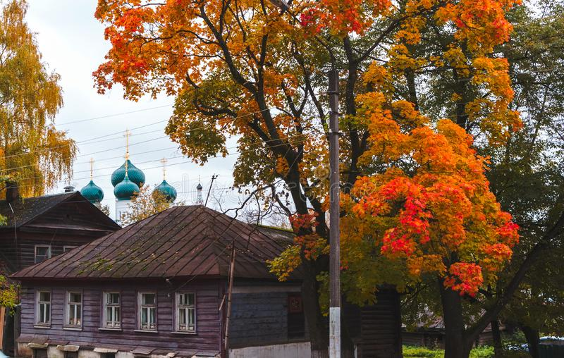 Wooden house, maple tree, Russian Orthodox Church on an autumn day in city of Kostroma, Russia stock photos