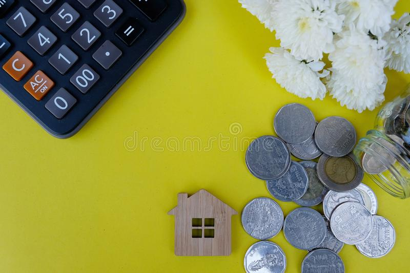 Wooden house model, calculator and coins on light yellow background. Property investment, Home finance concept stock photo