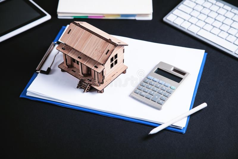Wooden house model with calculator and pen stock photo