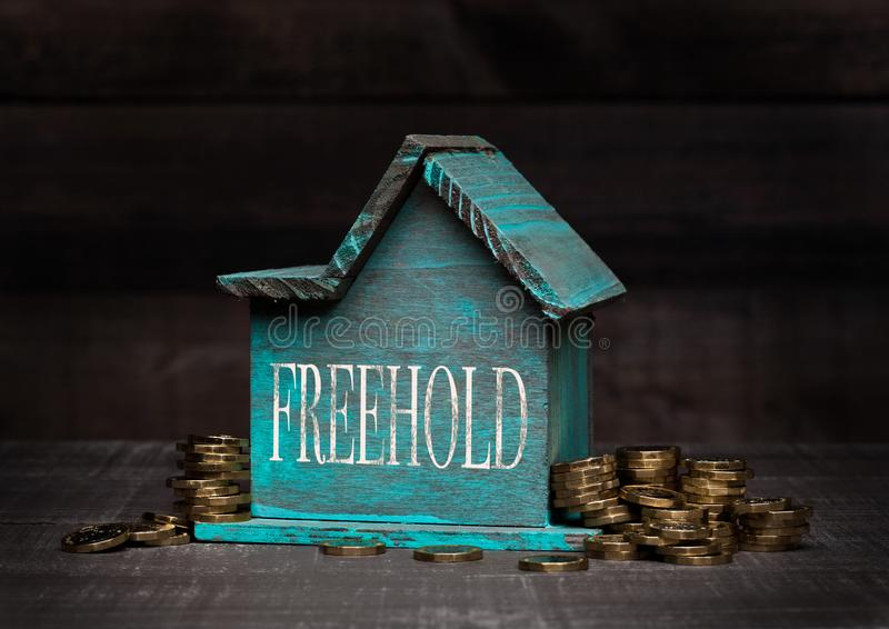 Wooden house model with coins next to it and hand. Wooden house model with coins next to it with conceptual text. Freehold stock photo