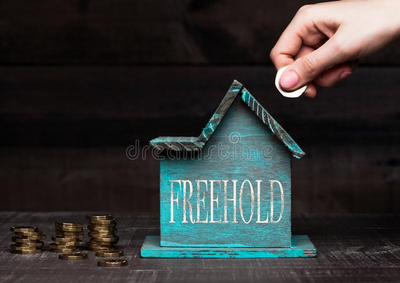 Wooden house model with coins next to it and hand. Holding the coin with conceptual text. Freehold stock image