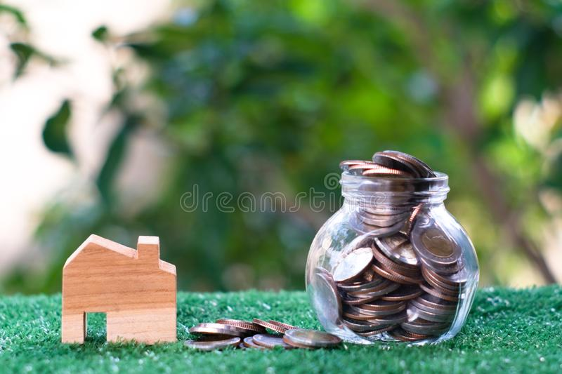 Wooden house model and glass jar with coins inside. Home mortgage and property investment concept. Copy space royalty free stock images
