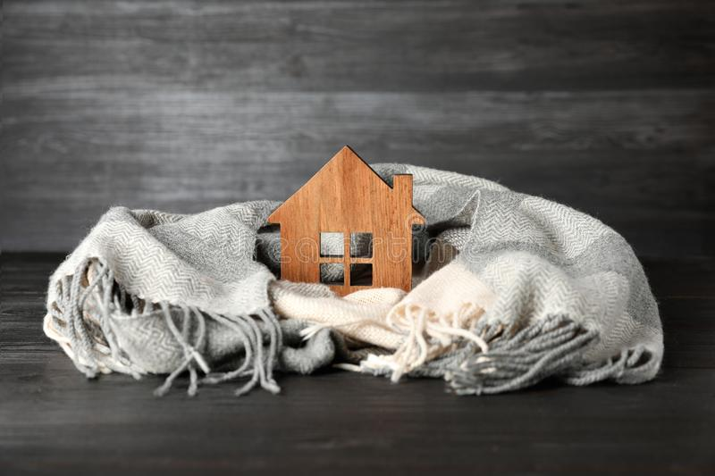 Wooden house model and  on grey table. Heating efficiency. Wooden house model and scarf on grey table. Heating efficiency royalty free stock photo