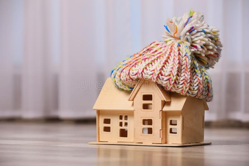Wooden house model in hat on floor indoors. Heating efficiency. Wooden house model in hat on floor indoors, space for text. Heating efficiency stock photos