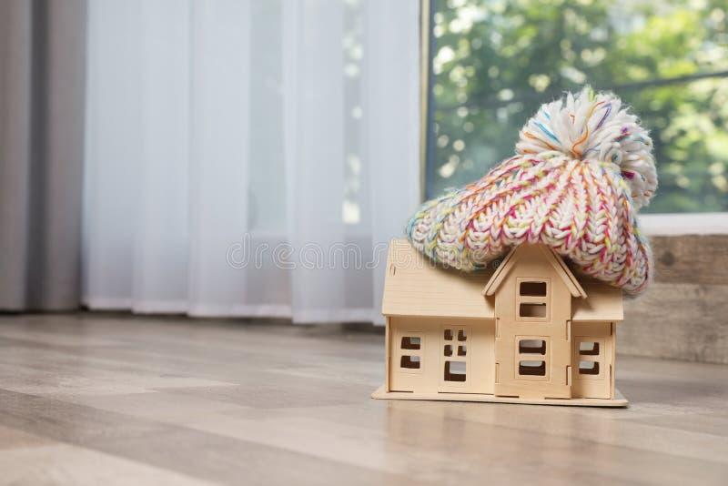 Wooden house model in hat on floor indoors. Heating efficiency. Wooden house model in hat on floor indoors, space for text. Heating efficiency stock image