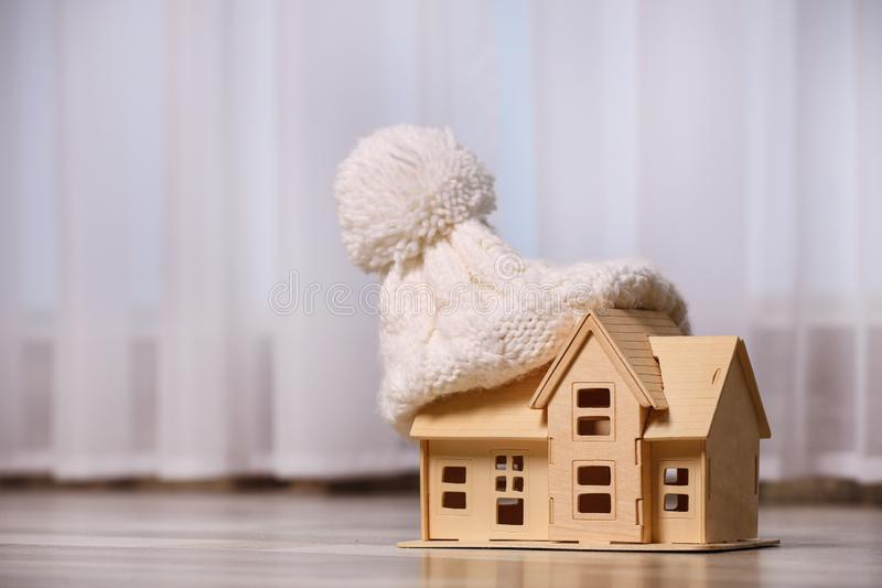 Wooden house model in hat on floor , space for text. Heating efficiency. Wooden house model in hat on floor indoors, space for text. Heating efficiency stock images