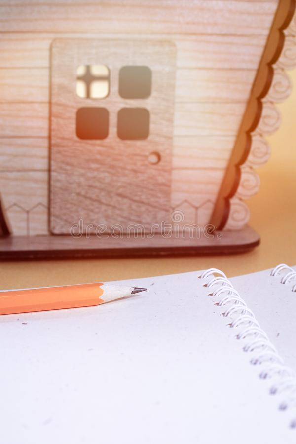 Wooden house model.Notebook.Toy wooden house close up. Toy wooden house close up.Wooden house model.Notebook stock photo