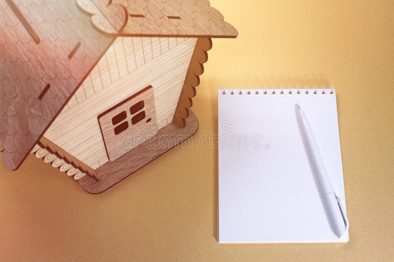 Wooden house model.Notebook.Toy wooden house close up. Toy wooden house close up.Wooden house model.Notebook royalty free stock photography