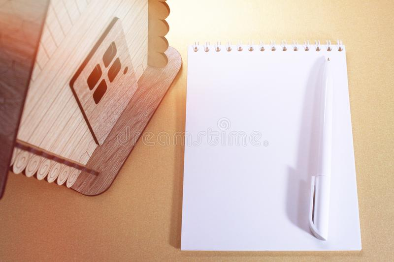 Wooden house model.Notebook.Toy wooden house close up. Toy wooden house close up.Wooden house model.Notebook royalty free stock image