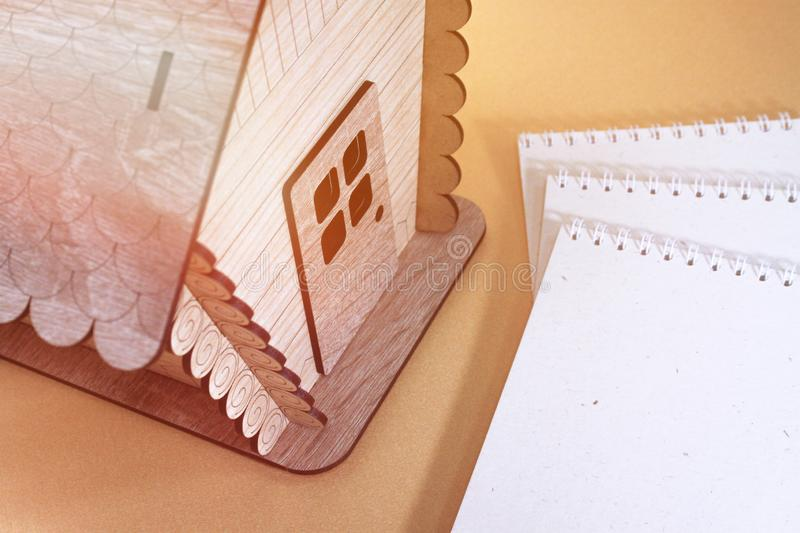Wooden house model.Notebook.Toy wooden house close up. Toy wooden house close up.Wooden house model.Notebook royalty free stock photos