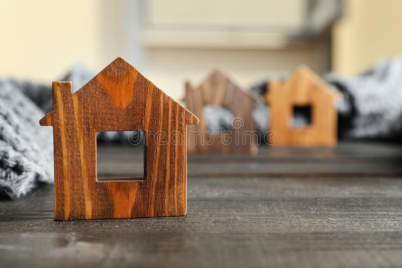 Wooden house model and scarf on grey , space for text. Heating efficiency. Wooden house model and scarf on grey table, space for text. Heating efficiency royalty free stock images