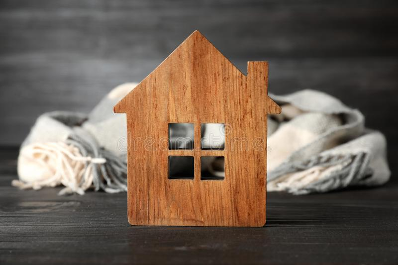 Wooden house model and scarf. Heating efficiency. Wooden house model and scarf on grey table. Heating efficiency royalty free stock photos