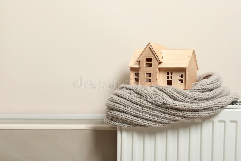 Wooden house model and scarf on  indoors, space for text. Heating efficiency. Wooden house model and scarf on radiator indoors, space for text. Heating stock images