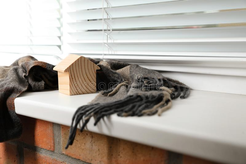 Wooden house model  scarf on window sill indoors, space for text. Heating efficiency. Wooden house model and scarf on window sill indoors, space for text stock photos