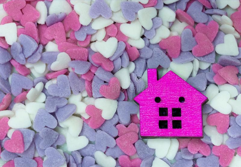 A wooden house model. A small wooden house model and colorful heat shape sugar confetti, warm, happy secured home concept stock image